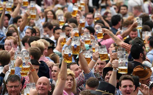 FILE PHOTO: People cheer with the pints of beer at the opening day of the 186th Oktoberfest in Munich, Germany Sep 21, 2019. REUTERS