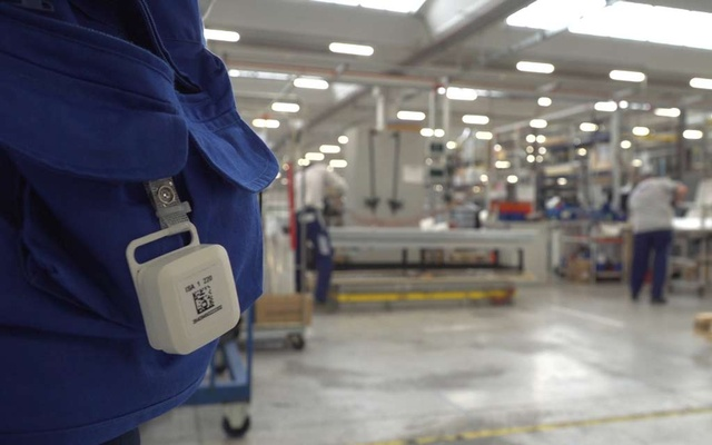 A tag using SWAT technology or System Workers Advance Tracing, which helps employees keep a safe social distance, hangs from a pocket of a worker inside the ISA factory in Bastia Umbra, Italy. REUTERS
