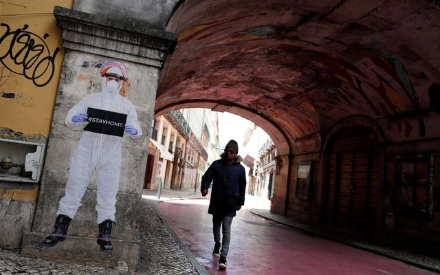 A man walks next to a picture of photographer Salvador Colaco in downtown Lisbon as the spread of the coronavirus disease (COVID-19) continues, Lisbon, Portugal, April 21, 2020. REUTERS/Rafael Marchante