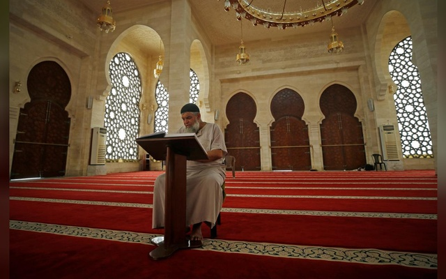 A Palestinian Muazzin, a person who calls for prayers, reads the Koran in an almost empty mosque on the first Friday of the holy fasting month of Ramadan as prayers by worshippers in the holy places are suspended due to concerns about the spread of the coronavirus disease (COVID-19) in the northern Gaza Strip April 24, 2020. REUTERS