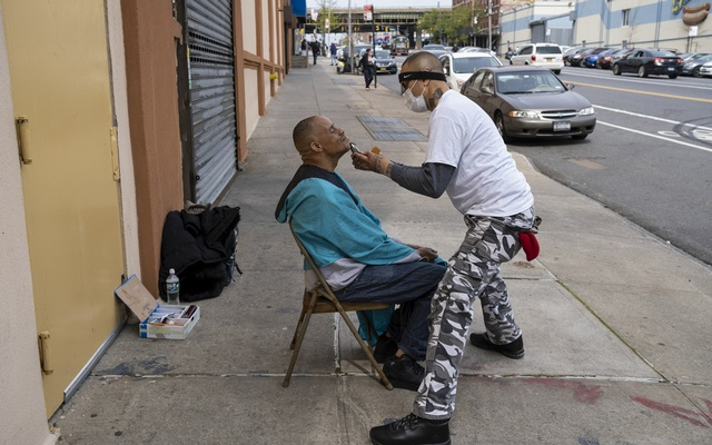 Dwayne Williams gets a haircut from his long time barber, Melo, in the Bronx, on Tuesday, April 21, 2020. The New York Times