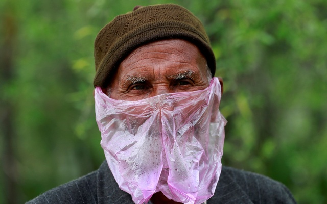 A man uses a plastic bag as a mask amid concerns about the spread of coronavirus disease (COVID-19), in Srinagar Apr 7, 2020. REUTERS
