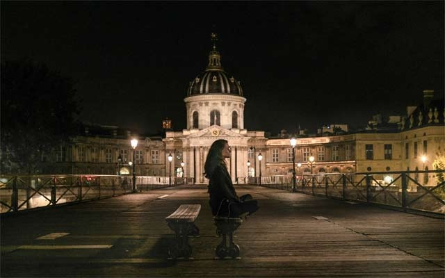 A person meditates on the Pont des Arts in Paris on April 20, 2020, during the coronavirus outbreak. The New York Times