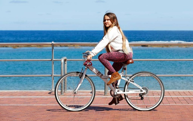 A girl rides her bike at promenade of Las Canteras beach after restrictions were partially lifted for children for the first time in six weeks, following the coronavirus disease (COVID-19) outbreak on the island of Gran Canaria, Spain, Apr 26, 2020. REUTERS