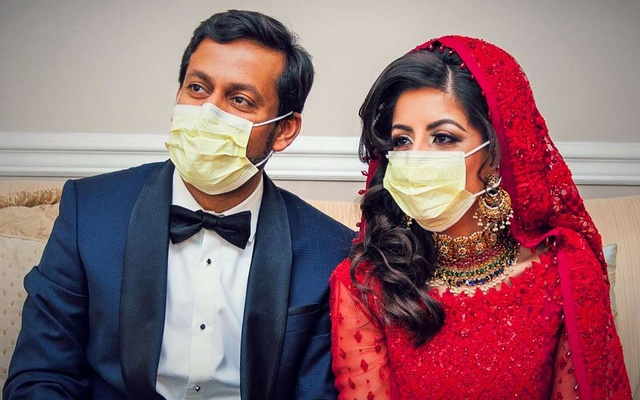 Doctors Kashif Chaudhry and Naila Shereen wear face masks after their wedding in New Windsor, New York, US, March 21, 2020 amid an outbreak of coronavirus disease (COVID-19). Picture taken March 21, 2020. Kashif Chaudhry and Naila Shereen/Handout via REUTERS
