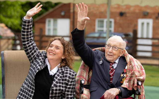 Former British Army Officer Captain Tom Moore and his daughter Hannah wave to a spitfire and hurricane from RAF Coningsby that fly over his house as part of celebration of his 100th birthday and a gesture of appreciation for his fundraising achievements for the NHS, in Bedfordshire, Britain, April 30, 2020. REUTERS