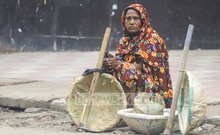 Sabita, a daily-wage worker who identified herself by a single name, waits for work on a street with her basket and spade at Pallabi in Dhaka. She was hoping that she will get something to do as the coronavirus lockdown has left a vast number of people jobless. Photo: Asif Mahmud Ove
