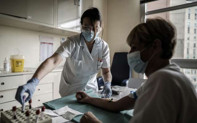 A health care worker performs a coronavirus antibody test at a hospital in Milan, April 30, 2020. The New York Times