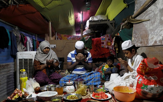 Rohingya refugees Taslima, 35, Zaffar Hussain, 39, and Shahid Hussain, 10, pray as Rizwan, 3, looks on before eating their Iftar meal at their house in a camp, during the fasting month of Ramadan and amid the outbreak of the coronavirus disease (COVID-19) in New Delhi, India April 30, 2020. REUTERS/Anushree Fadnavis