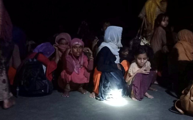 Rohingya refugees who were rescued by Bangladesh Coast Guard, sit on the shore in Teknaf, subdistrict of Cox's Bazar, Bangladesh April 15, 2020. Abdul Aziz/Handout via REUTERS