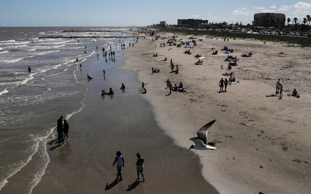 A seagull flies over beach goers after a state wide partial-reopening of the economy during the coronavirus disease (COVID -19) pandemic in Galveston, Texas, US, May 3, 2020. REUTERS