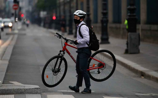 A man wearing a protective face mask carries his bike in the Rue de Rivoli in Paris during the outbreak of the coronavirus disease in France on May 5. REUTERS