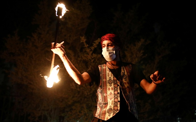A man plays with fire next to a festive Ramadan float as it drives through a street in East Jerusalem to bring celebrations to people under the coronavirus disease (COVID-19) movement restrictions, May 3, 2020. Picture taken on May 3, 2020 REUTERS