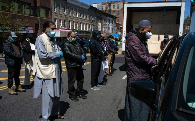 Imam Ahmed Ali Uzir, right, leads a prayer outside Al-Rayaan Muslim Funeral Services in Brooklyn in front of a minivan that will take the deceased to a cemetery on Long Island on April 28, 2020. The number of funerals at Al-Rayaan has risen to about 15 each day, compared to 20 to 30 a month before the coronavirus arrived. (Todd Heisler/The New York Times)