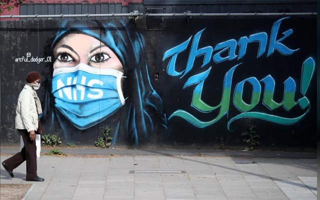 A person wearing a protective face mask walks past streetart 'NHS Dedication Mural' by The Artful Dodger (A Dee) in Elephant & Castle, following the outbreak of the coronavirus disease (COVID-19), London, Britain, May 5, 2020. REUTERS