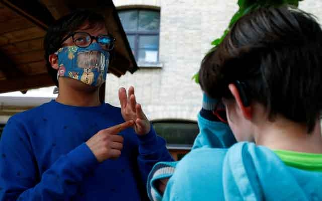 Educator Nicolas, wearing a partially transparent mask, uses sign language to communicate with a student at the Royal Institute for the Deaf Mute, amid the coronavirus disease (COVID-19) outbreak, in Brussels, Belgium, May 4, 2020. Reuters