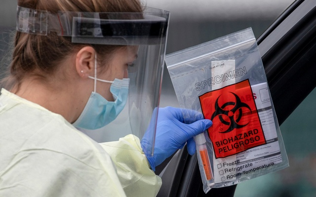 A health worker in protective gear hands out a self-testing kit in a parking lot of Rose Bowl Stadium during the global outbreak of the coronavirus disease (COVID-19), in Pasadena, California, US, Apr 8, 2020. REUTERS