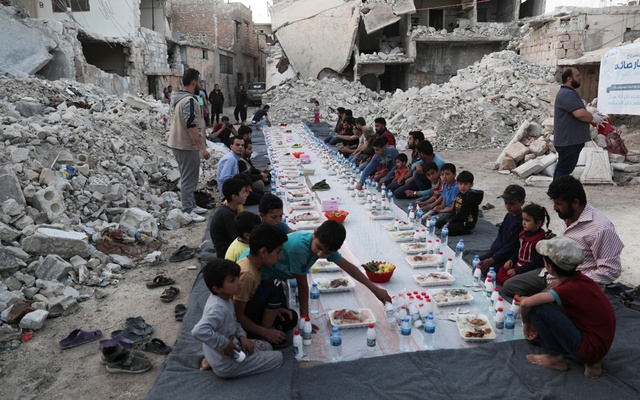 People wait the call to prayer before they eat their Iftar meal provided by a group of volunteers, in a damaged neighbourhood, amid fear for the coronavirus disease (COVID-19) outbreak, in Atarib, Aleppo countryside Syria May 7, 2020. REUTERS