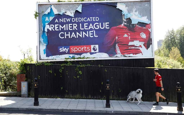A man walks his dog past a Sky Sports Premier League advert in Stockport, following the outbreak of the coronavirus disease (COVID-19), Stockport, Britain, May 7, 2020. REUTERS/Phil Noble