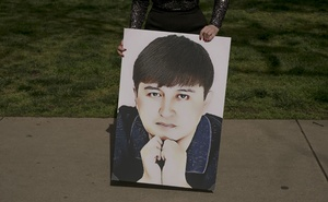 Rayhan Asat holds a portrait of her brother, Ekpar, in Washington, April 27, 2020. The New York Times