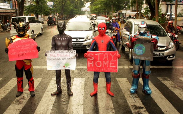 Volunteers wearing superhero costumes carry banners for a campaign against the spread of the coronavirus disease (COVID-19) in Makassar, South Sulawesi, Indonesia, Apr 17, 2020. REUTERS
