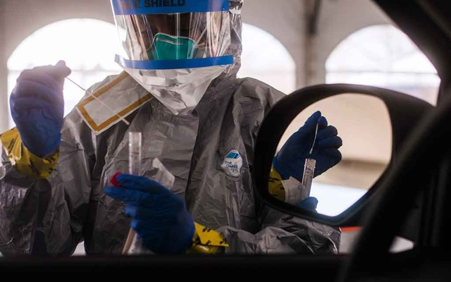 FILE -- A health care worker holds a swab at a drive-through testing centre for the coronavirus in New Rochelle, N.Y., March 16, 2020. (Andrew Seng/The New York Times)