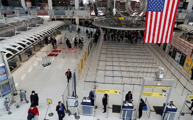 Passengers walk through Terminal 1, after further cases of coronavirus were confirmed in New York, at JFK International Airport in New York, US, March 13, 2020. REUTERS