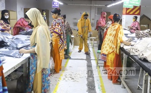 A cleaner wearing protective gear sprays disinfectant at a readymade garment factory in Dhaka's Mirpur amid the coronavirus outbreak. Photo: Asif Mahmud Ove