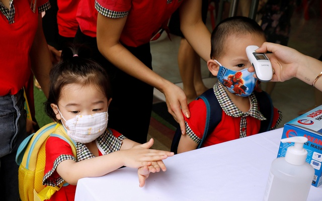 Kindergarten students clean hands and have their temperatures checked while arriving to their first day of class after the government eased a nationwide lockdown during the coronavirus disease (COVID-19) outbreak in Hanoi, Vietnam May 11, 2020. REUTERS