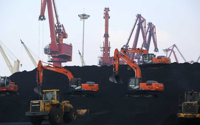 Workers operate loaders to unload imported coal at a port in Lianyungang, Jiangsu province, China. REUTERS