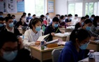 Students wearing face masks are seen inside a classroom during a government-organised media tour at a high school as more students returned to campus following the coronavirus disease (COVID-19) outbreak, in Shanghai, China May 7, 2020. REUTERS