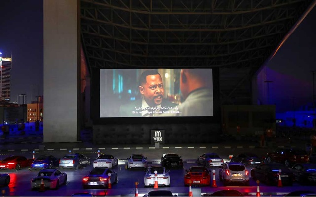People sit in their cars watching a movie in a drive-in cinema at the Mall of the Emirates, following the outbreak of the coronavirus disease (COVID-19), in Dubai, United Arab Emirates, May 13, 2020. REUTERS