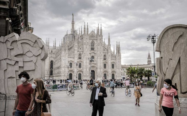 Crowds pass by the Piazza Duomo in Milan, May 10, 2020. Countries across Europe, eyeing the summer holidays, are taking steps to begin reopening borders that had been closed to prevent the spread of coronavirus. (Alessandro Grassani/The New York Times)
