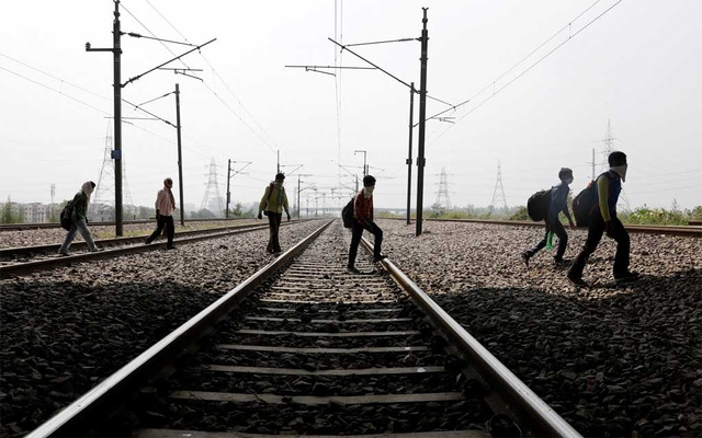 Migrant workers carrying their belongings and with their faces covered walk along a railway track to return to their home state of eastern Bihar, during an extended nationwide lockdown to slow the spread of the coronavirus disease (COVID-19), in Ghaziabad, in the outskirts of New Delhi, India, May 13, 2020. REUTERS