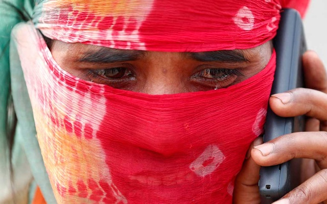 The wife of a migrant worker cries as she talks to a relative on a mobile phone after police stopped them at a checkpoint while they were walking on a highway to return to their home state in the northern state of Uttar Pradesh, during an extended nationwide lockdown to slow the spread of the coronavirus disease (COVID-19), in Ghaziabad, in the outskirts of New Delhi, India, May 13, 2020. REUTERS
