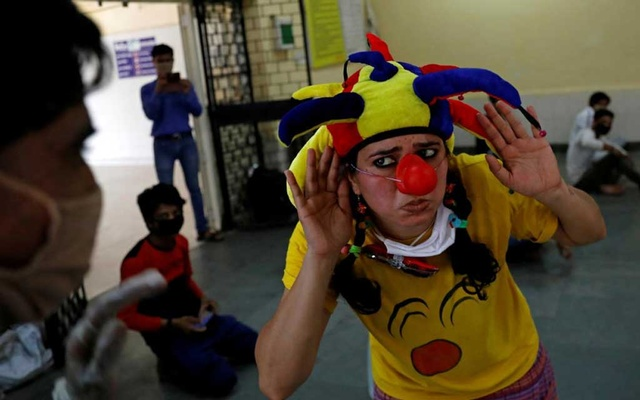 Sheetal Agarwal, 34 and a medical clown, reacts as she performs for people at a shelter, during an extended nationwide lockdown to slow the spread of the coronavirus disease (COVID-19), in New Delhi, India, May 2, 2020. REUTERS