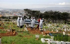 Family members and funeral workers carry the coffin of a 51-year-old man who died from the coronavirus disease (COVID-19), at a cemetery in Cape Town, South Africa, May 12, 2020. REUTERS