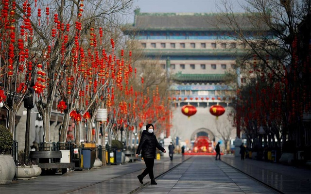 A woman wearing a face mask walks on the Qianmen pedestrian street in the morning after the extended Lunar New Year holiday caused by the novel coronavirus outbreak, in Beijing, China Feb 10, 2020. REUTERS