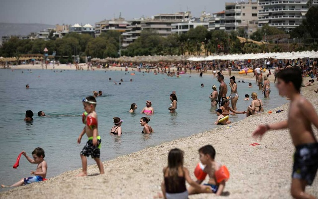 People enjoy the sun during the official reopening of beaches to the public following the easing of measures against the spread of the coronavirus disease (COVID-19), in Athens, Greece, May 16, 2020. REUTERS