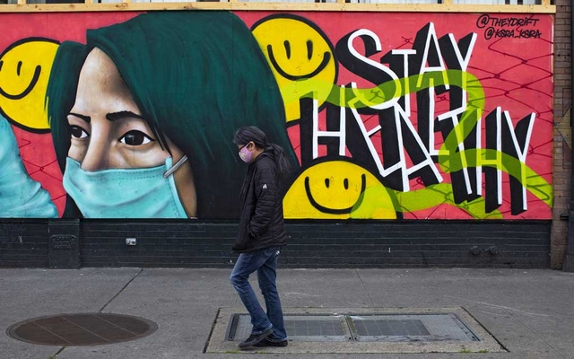 FILE -- A pedestrian with a face mask walks past a mural in Seattle, May 5, 2020. An innovative coronavirus testing program in the Seattle area that involved sending home test kits to both healthy and sick people has been ordered by the federal government to stop its work pending additional reviews. (Ruth Fremson/The New York Times)