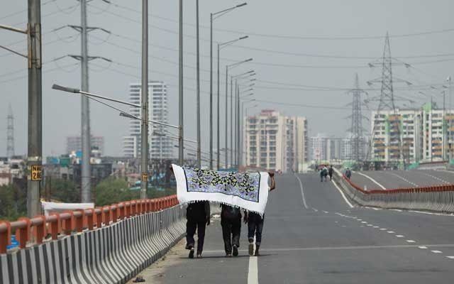 Migrant workers hold a bedsheet to protect themselves from the sun on a national highway as they walk towards their home state of Uttar Pradesh, during an extended nationwide lockdown to slow the spread of the coronavirus disease (COVID-19), in Ghaziabad, in the outskirts of New Delhi, India, May 14, 2020. Reuters