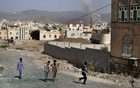 FILE -- Smoke rises from an airstrike in the background as residents walk towards the site of another strike that killed several people, in Sana, Yemen, on Sept. 5, 2015. President Donald Trump sees arms deals as jobs generators for firms like Raytheon, which has made billions in sales to the Saudi coalition, the Obama administration initially backed the Saudis too, but later regretted it as thousands died. (Tyler Hicks/The New York Times)