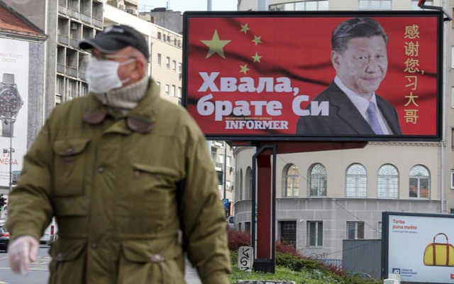 FILE PHOTO: A man wearing a protective mask passes by a billboard depicting Chinese President Xi Jinping as the spread of the coronavirus disease (COVID-19) continues in Belgrade, Serbia, April 1, 2020. The text on the billboard reads