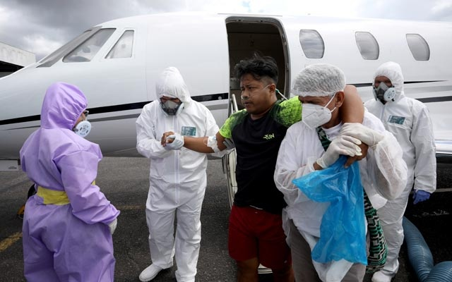 Javier Alexndre Andres Cruz, 26, a Tikuna indigenous man and a patient, who suffers from the coronavirus disease (COVID-19), is helped by healthcare workers as he arrives from Tabatinga to Manaus, Brazil, May 18, 2020. REUTERS