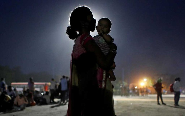 A woman and her baby wait for a bus to take them to a railway station to board a train to their home state of Uttar Pradesh, after a limited reopening of India's giant rail network following a nearly seven-week lockdown to slow the spreading of the coronavirus disease (COVID-19), in Ghaziabad in the outskirts of New Delhi, May 18, 2020. REUTERS