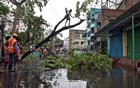 A man cuts branches of an uprooted tree after Cyclone Amphan made its landfall, in Kolkata, India, May 21, 2020. REUTERS