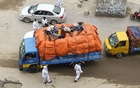 Travellers lie on a goods-laden truck to hide from the police at a check-post set up in Dhaka's Uttara to control the movement of people in and out of the city as part of efforts to slow the spread of coronavirus. Photo: Asif Mahmud Ove