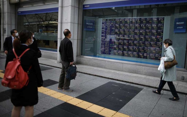 FILE PHOTO: People wearing protective face masks, following an outbreak of the coronavirus disease (COVID-19), look at a stock quotation board outside a brokerage in Tokyo, Japan, March 10, 2020. REUTERS/Stoyan Nenov