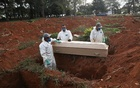 Gravediggers wearing protective suits prepare to bury the coffin of a person who died from the coronavirus disease (COVID-19) during a ceremony with no relatives, at Vila Formosa cemetery, Brazil's biggest cemetery, in Sao Paulo, Brazil, May 22, 2020. REUTERS