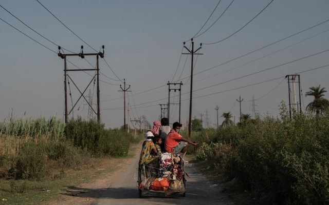 Migrants travel home by cycle rickshaw from Punjab to Bihar in the village of Andhel, India, May 16, 2020. During the past two months under India's coronavirus lockdown, millions of migrant laborers and their families have poured out of India's cities, desperate and penniless, as they try to get back to their native villages where they can rely on family networks to survive. (Rebecca Conway/The New York Times)